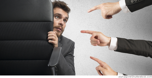 fingers pointing at businessman behind chair